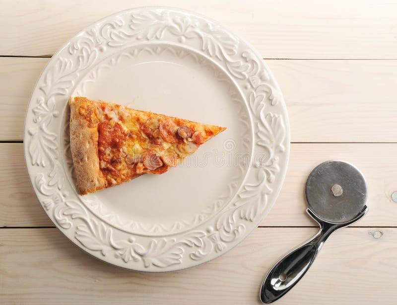 Tranche de pizza avec du fromage et les saucisses épicées d'un plat image libre de droits