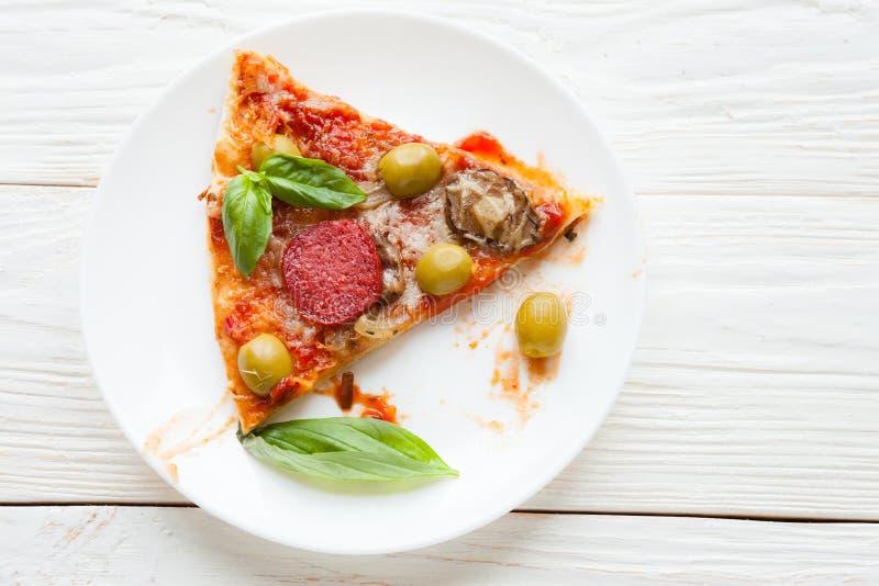Tranche de pizza avec le salami et de basilic du plat blanc image stock