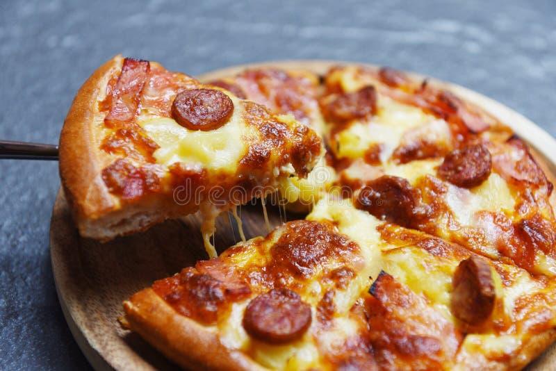 Tranche de pizza sur le fond foncé/fromage traditionnel italien savoureux délicieux de pizza d'aliments de préparation rapide photo stock