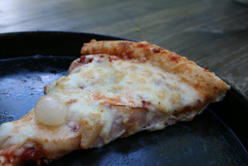 Tranche de pizza sur une casserole sur une table en bois images stock