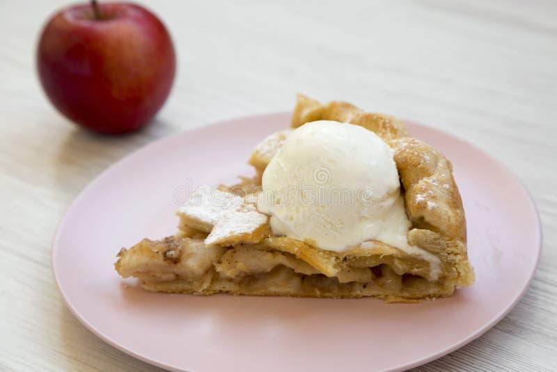 Tranche de tarte aux pommes faite à la maison avec la glace du plat rose au-dessus du fond en bois blanc, vue de côté images libres de droits