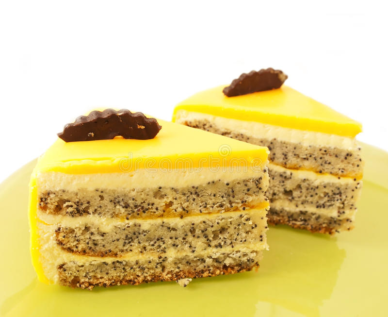 Tranche deux de gâteau délicieux de mangue avec le pavot du plat vert photographie stock