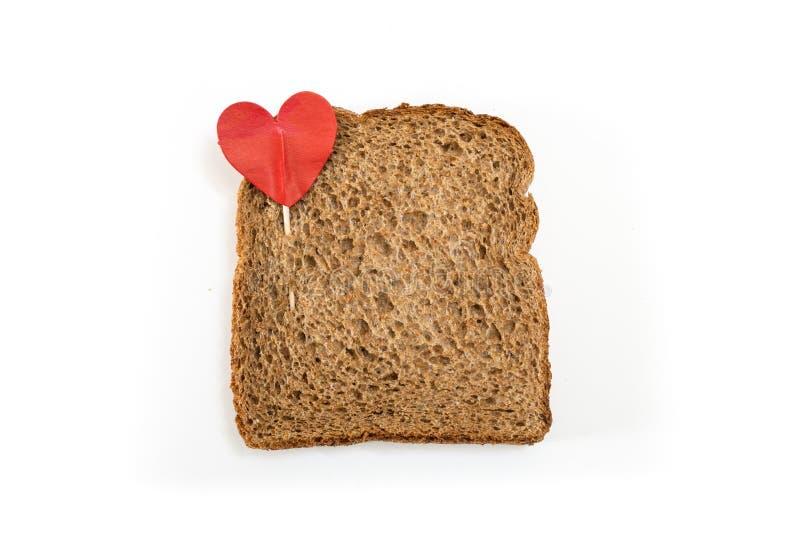 Tranche entière de pain de sandwich à grain avec la goupille de coeur, sur le fond blanc image libre de droits