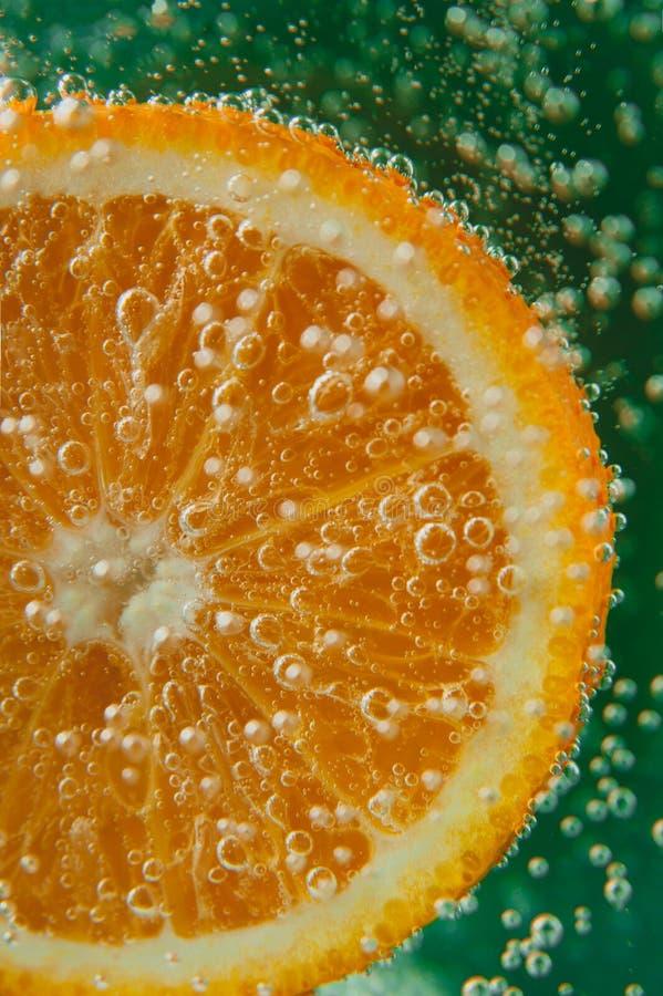 Tranche orange dans l'eau avec des bulles image stock