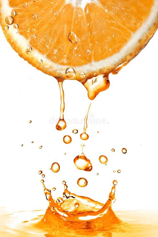 Tranche orange et éclaboussure de jus d'isolement sur le blanc photographie stock libre de droits