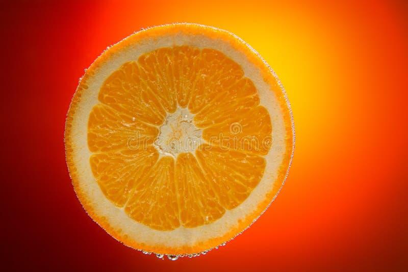 Tranche orange fraîche dans l'eau avec des bulles sur le dos orange de gradient photographie stock libre de droits