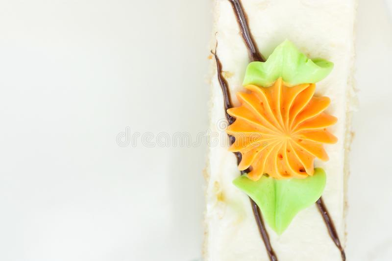 Tranche rectangulaire de gâteau de couche d'éponge avec le givrage fouetté de crème de beurre Décoré de Daisy Flower orange color photographie stock