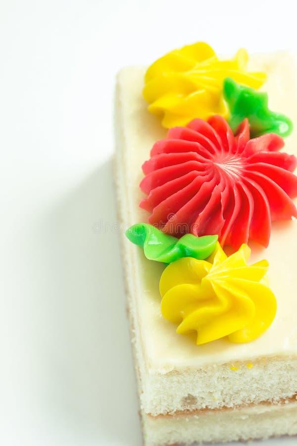 Tranche rectangulaire de gâteau de couche d'éponge avec le givrage fouetté de crème de beurre Décoré de Daisy Flowers jaune rouge photographie stock libre de droits