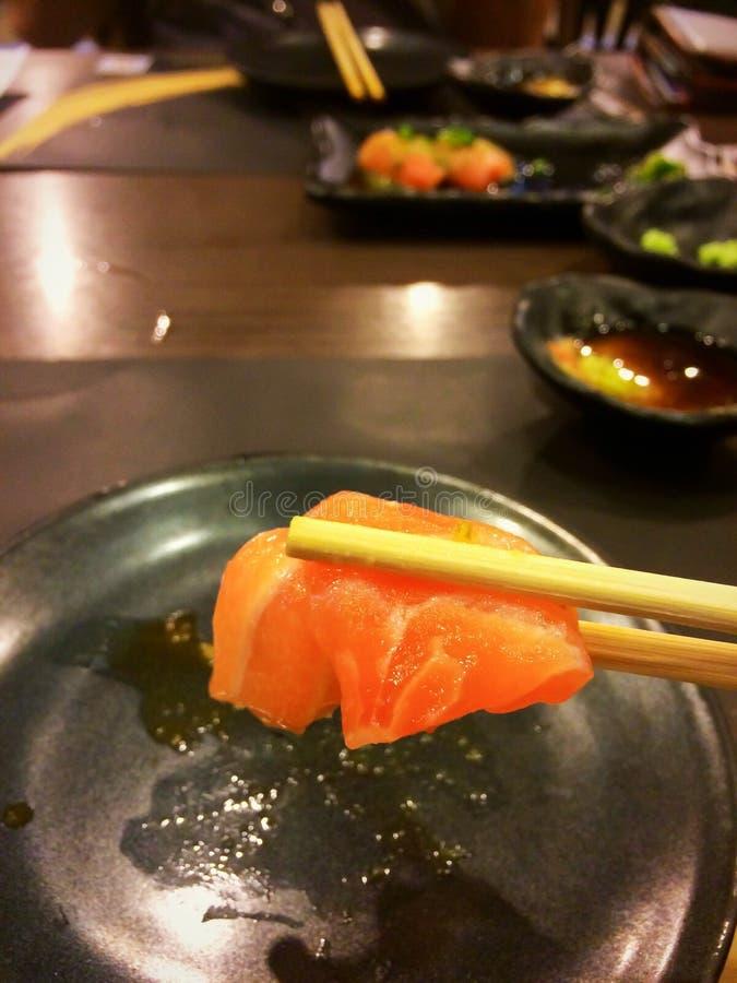 Tranche saumonée de sashimi en baguettes en bois pour le repas photo stock