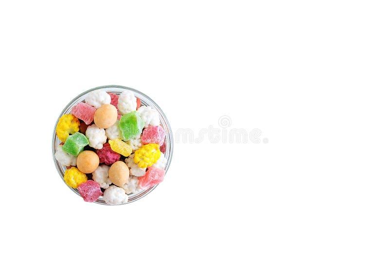 Tranches, écrous et sucreries de fruits secs dans le lustre dans un bol en verre isolat blanc image stock