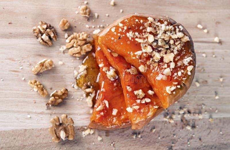 Tranches appétissantes de potiron avec du miel et des noix image stock