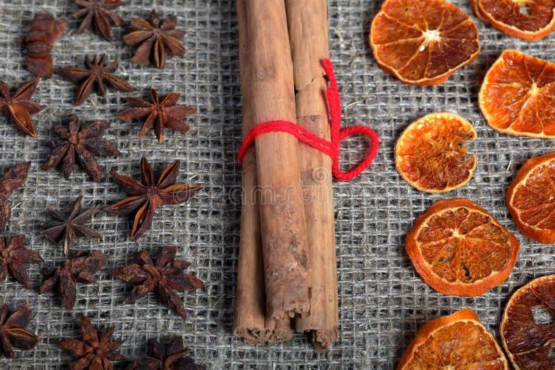 Tranches, cannelle et anis oranges secs pour la décoration Présenté sur un tissu de toile rugueux image libre de droits
