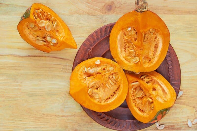 Tranches crues de potiron avec des graines du plat brun sur le fond en bois Ingrédients pour la soupe savoureuse à automne photos libres de droits