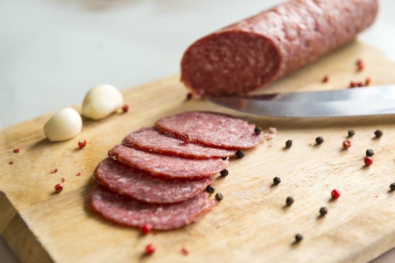 Tranches découpées en tranches de salami avec les épices et l'ail sur le panneau en bois, couteau photo libre de droits