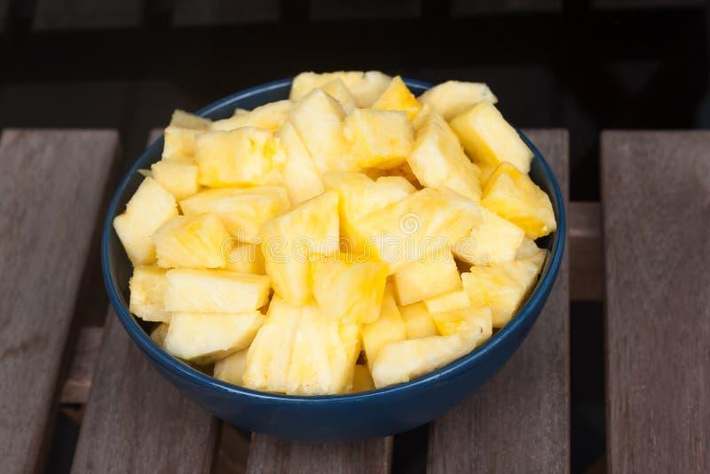Tranches d'ananas dans une boule bleue sur un fond en bois images libres de droits