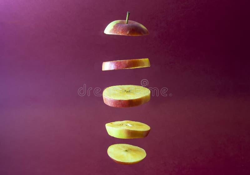 Tranches d'Apple de vol avec le fond rouge photo stock