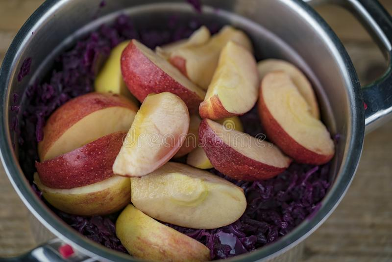Tranches d'Apple sur le chou rouge dans la casserole images stock