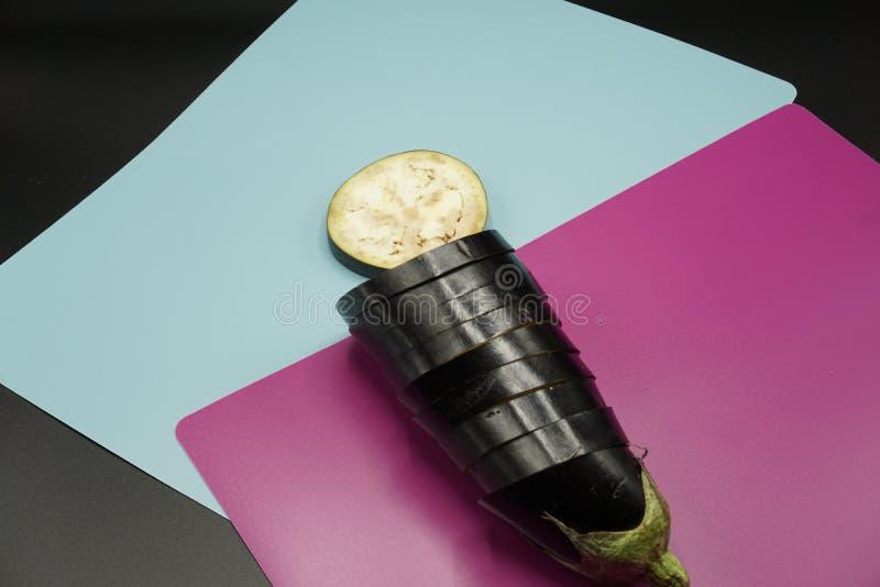 Tranches d'aubergine disposées dans une conception abstraite sur le fond vibrant de couleur photo stock