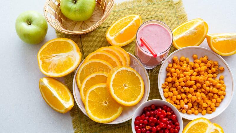 Tranches d'oranges et de fruit avec le detox sur la table Vue de ci-avant image stock