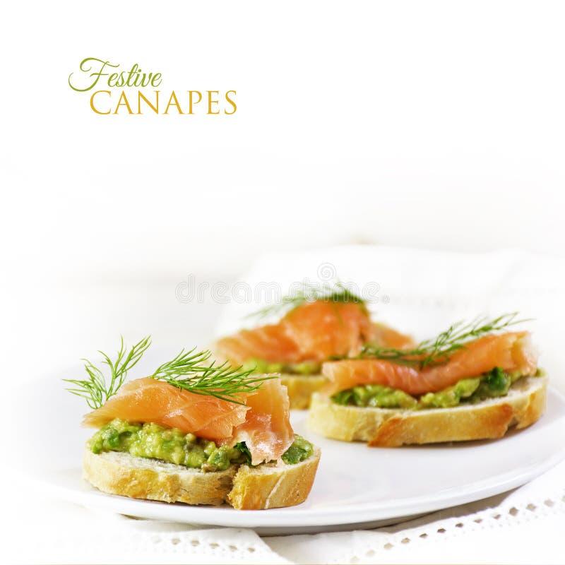 Tranches de baguette avec les saumons fumés et la crème ou le guacamol d'avocat photo stock