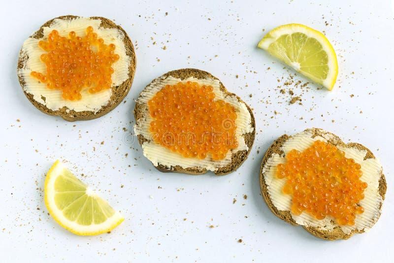 3 tranches de baguette enduites du beurre et du caviar rouge sur le fond blanc Configuration plate Sandwichs et citron rouges à c photo stock