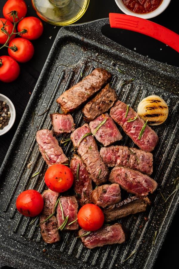 Tranches de bifteck juteux avec des tomates-cerises sur la casserole de gril photo stock
