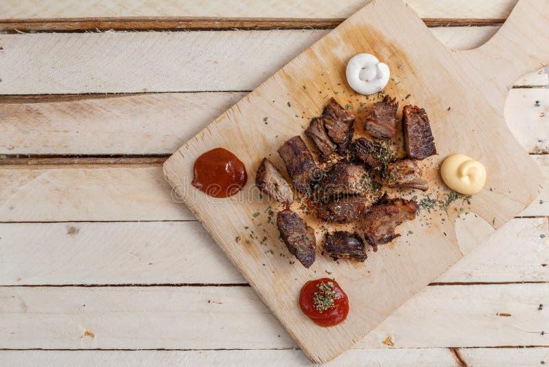 Tranches de boeuf frit sur une cuvette en bois avec différents types de sauces sur un fond en bois clair photo stock