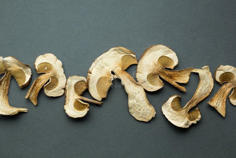 Tranches de champignons secs de boletus sur le fond noir photos stock