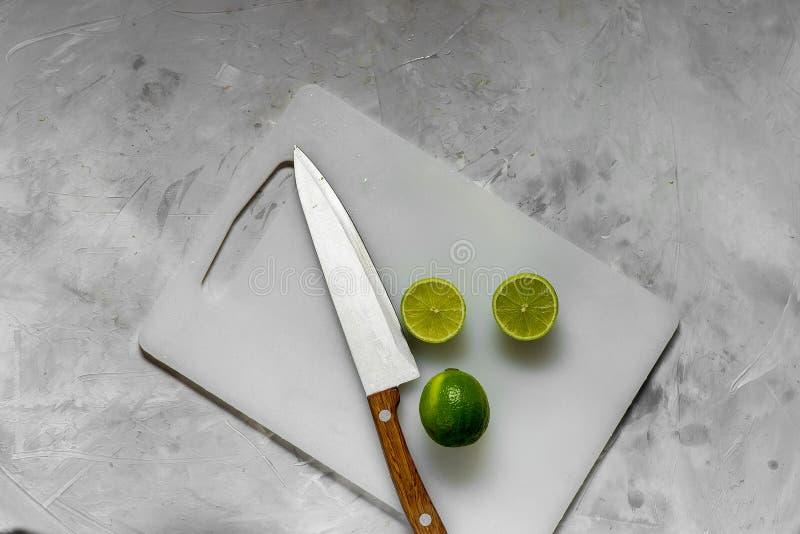 Tranches de chaux verte fraîche sur le panneau de lumière de cuisine photographie stock