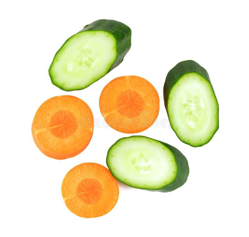 Tranches de concombre et de carotte sur le blanc image libre de droits