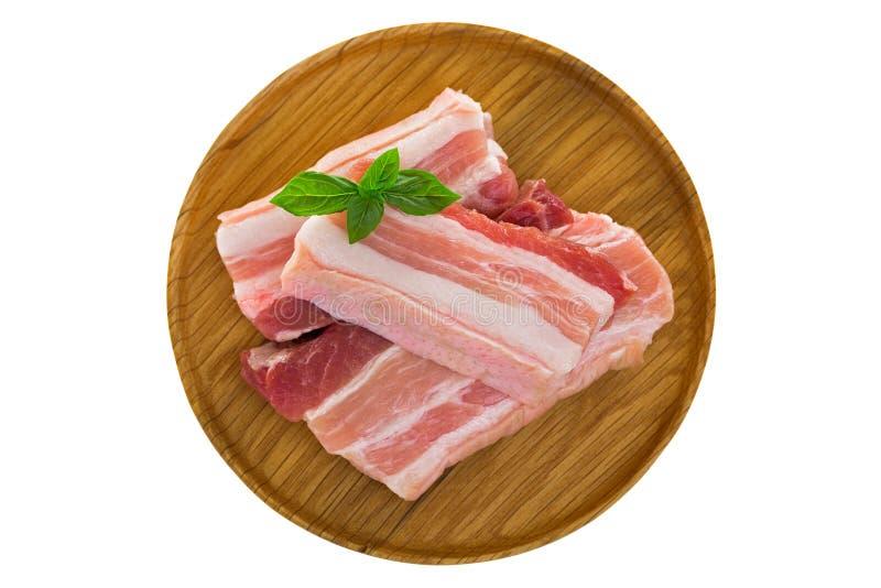 Tranches de coupe fraîche crue de ventre de porc du plat en bois d'isolement sur W photos libres de droits