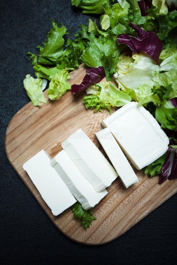 Tranches de feuilles de feta et de laitue sur une planche à découper photos libres de droits