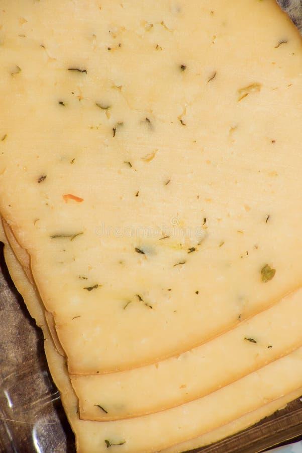 Tranches de fromage jaune avec des herbes et des épices images stock