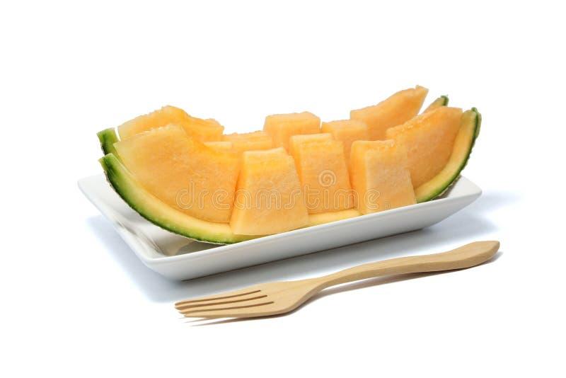 Tranches de fruit de melon d'un plat blanc avec la fourchette en bois photographie stock