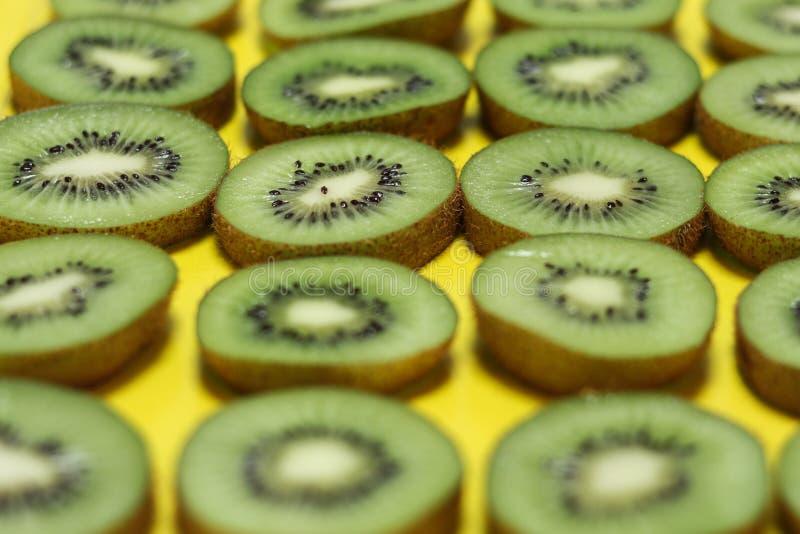 Tranches de kiwi avec le fond jaune images libres de droits