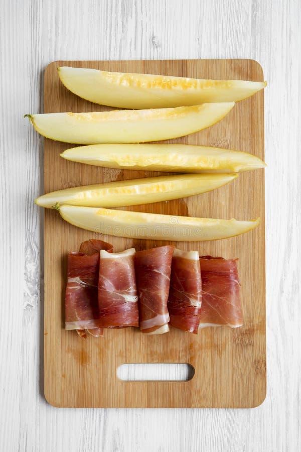 Tranches de melon avec le prosciutto sur le conseil en bambou au-dessus du fond en bois blanc image libre de droits