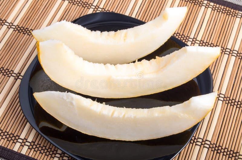 Tranches de melon juteux sur un plan rapproché de plat noir photos libres de droits