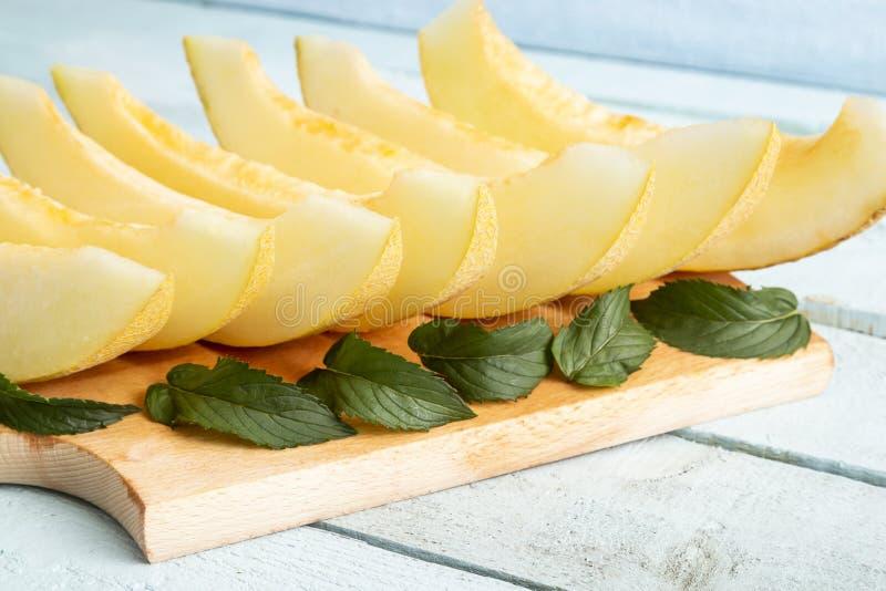 Tranches de melon sur une planche à découper photos stock