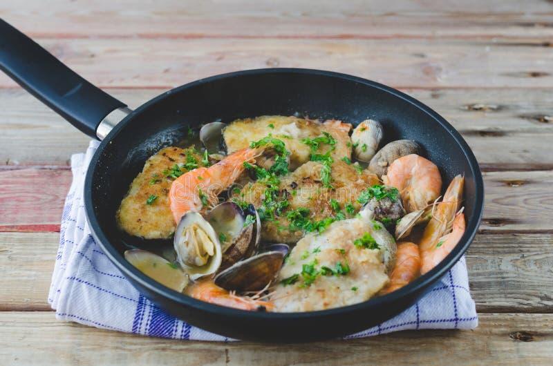 Tranches de merluches cuites avec des crevettes roses et des palourdes photographie stock