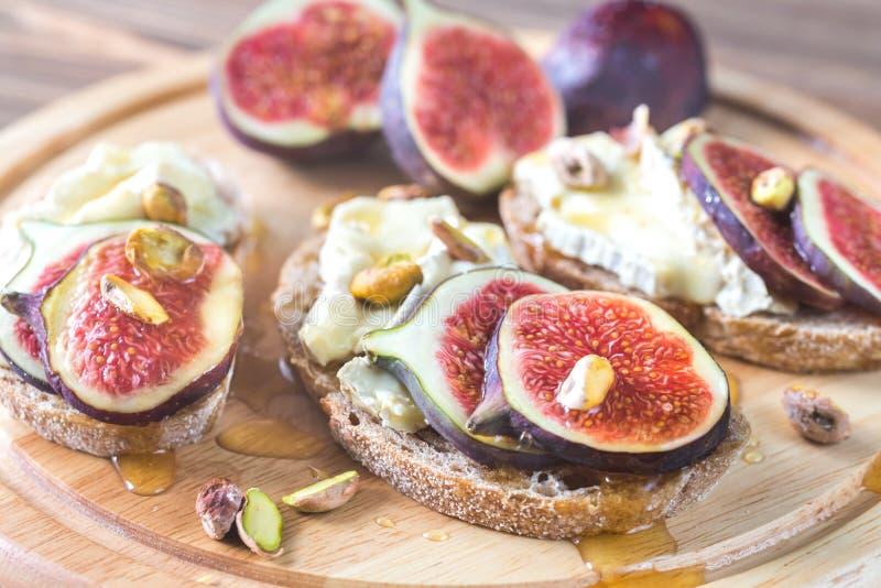 Tranches de pain avec le camembert, les figues et les pistaches photos stock