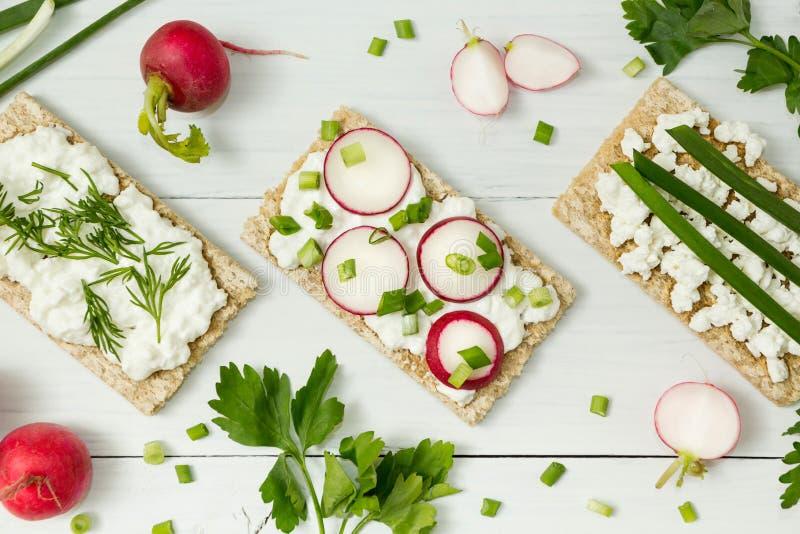 Tranches de pain avec le fromage fondu, tranches de radis et ciboulette sur le conseil en bois image stock