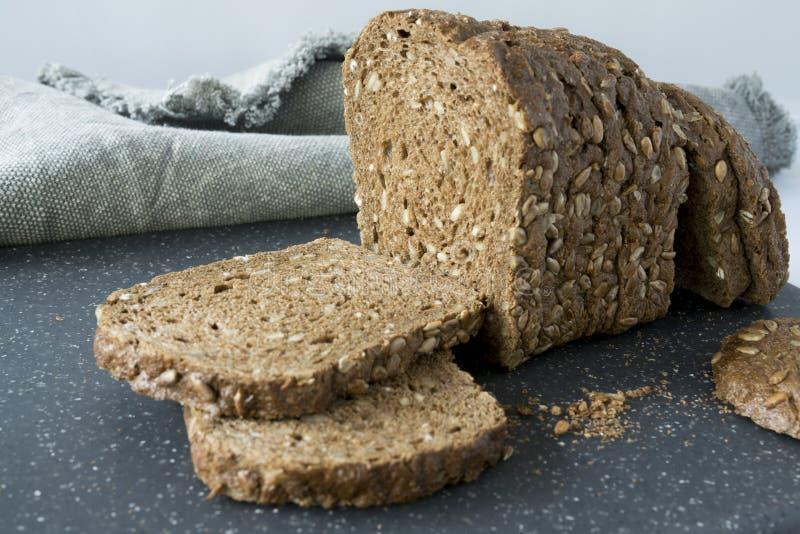 Tranches de pain brun de grain entier avec la graine de tournesol, sur une planche à découper grise photographie stock