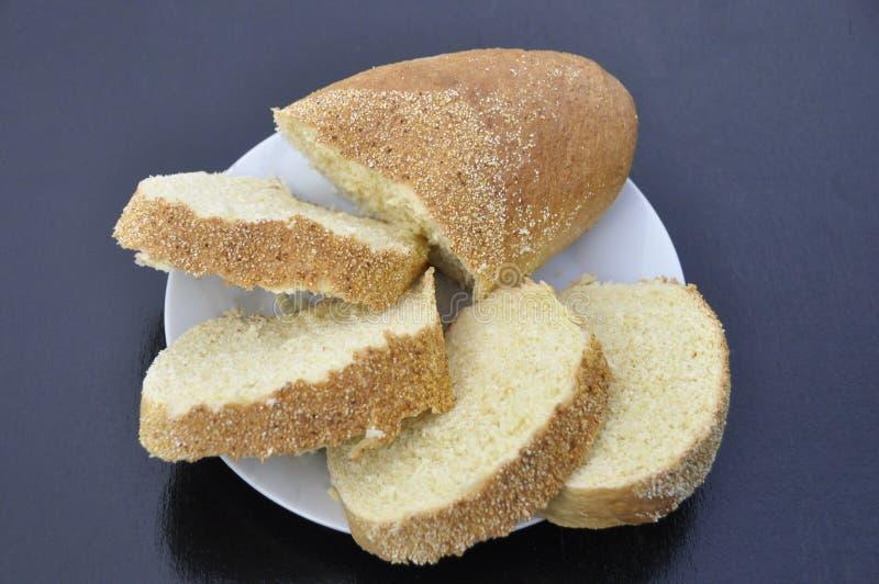 Tranches de pain coupé en tranches avec la farine d'avoine dans un plat blanc sur un fond foncé photographie stock libre de droits