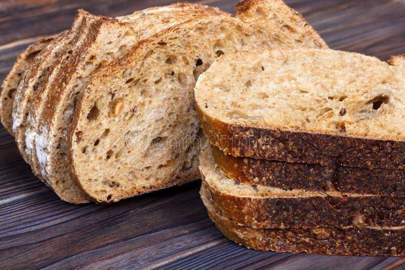 Tranches de pain frais sur la planche à découper sur le fond en bois blanc photos stock