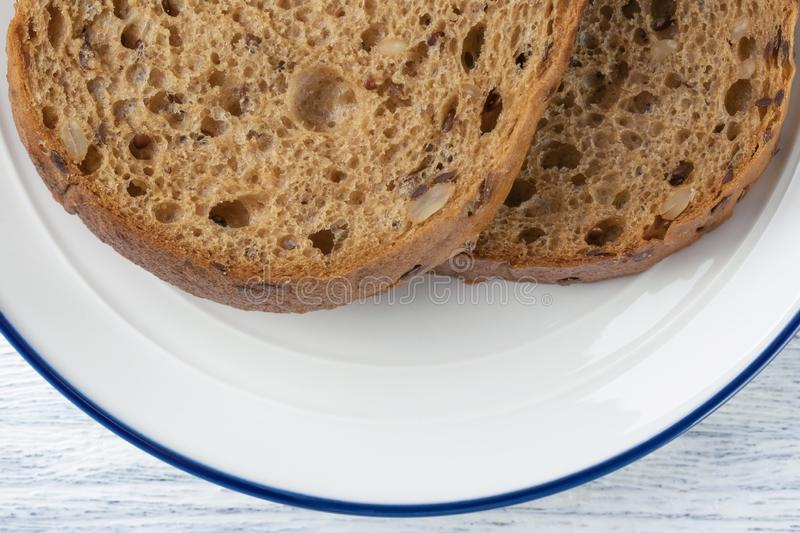 Tranches de pain de grain avec le moule D'un plat blanc avec une rayure bleue Sur une table en bois photos libres de droits