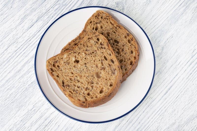 Tranches de pain de grain avec le moule D'un plat blanc avec une rayure bleue Sur une table en bois photos stock