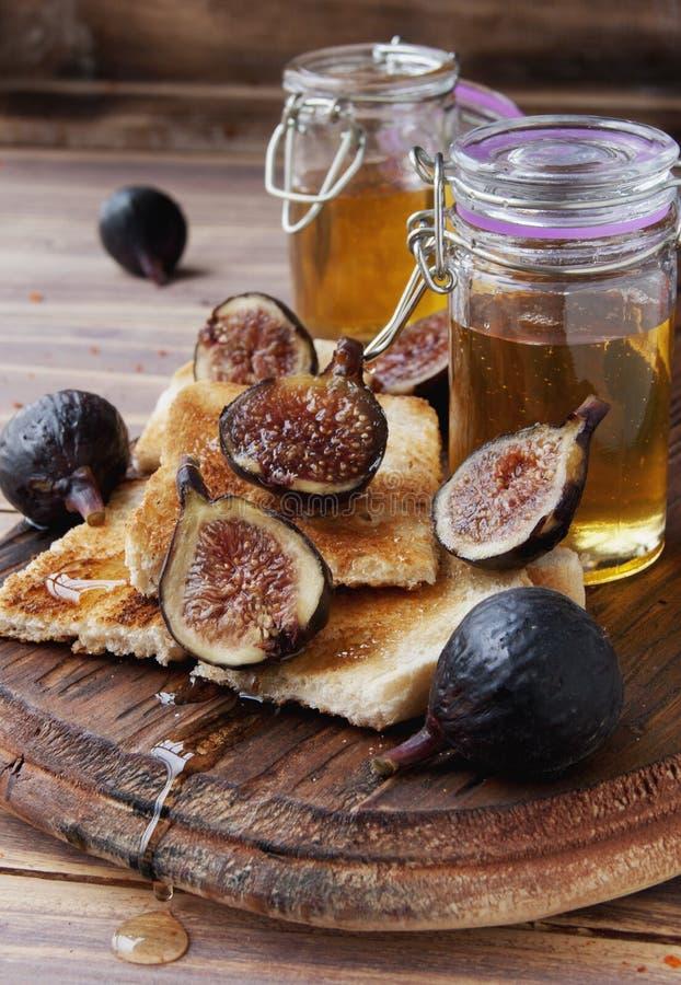 Tranches de pain grillé avec les figues et le miel photo stock