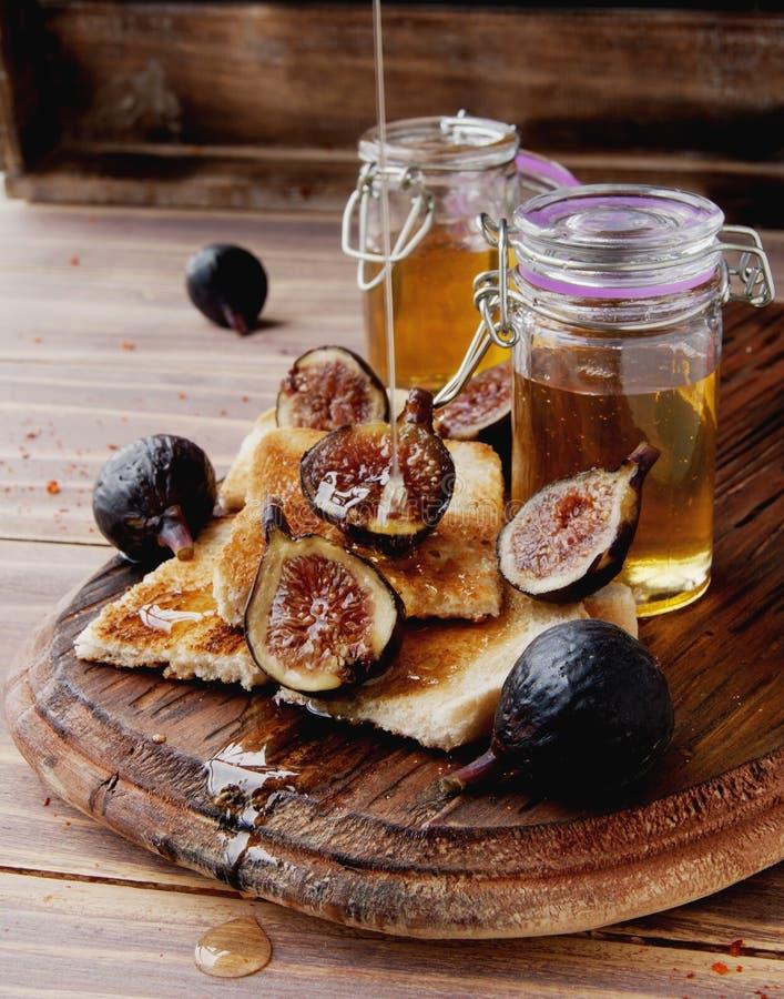 Tranches de pain grillé avec les figues et le miel photo libre de droits