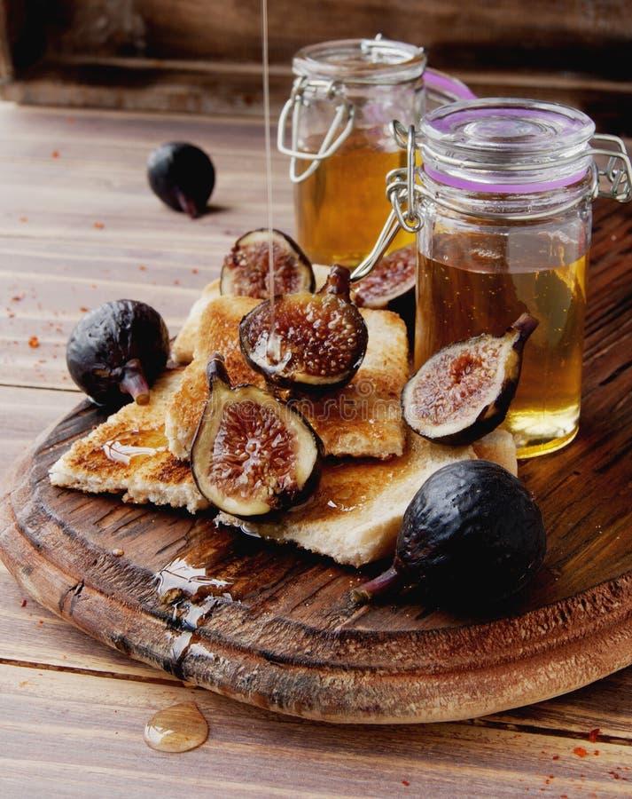 Tranches de pain grillé avec les figues et le miel image libre de droits