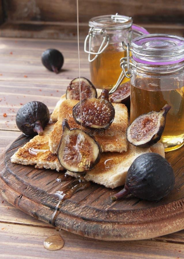 Tranches de pain grillé avec les figues et le miel image stock
